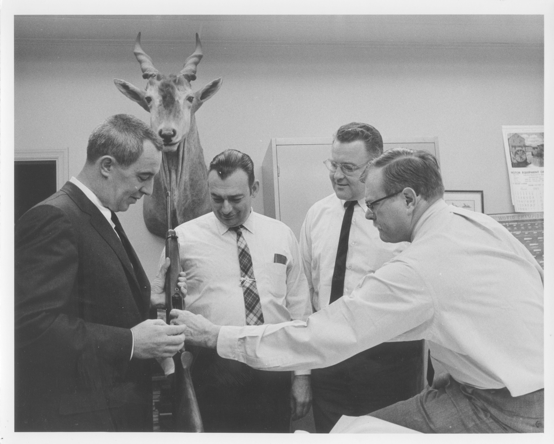 L-R, Ed Nolan VP of marketing, Harry Sefried	 chief engineer, Michael Horelick VP of manufacturing and Bill Ruger seen here discussing the rotary magazine feature of the 10/22 carbine.  This image was taken in the design studio in the Lacey Place factory 1963-64.  These men have all passed on. Notice Harry's tie clip.